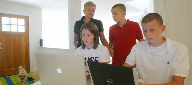 Kel Kelly, back left, and her children Julia McGovern, 18, front left, Shaun McGovern, 16, right, and Patrick McGovern, 14, gather around their computers at their vacation home in Wellfleet, Mass., Wednesday, July 30, 2008. Some parents are concerned about the way Facebook has changed the way children interact with each other.