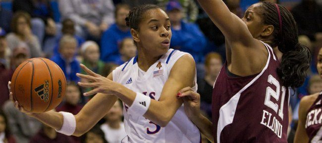 In this file photo from Jan. 21, 2012, Kansas University guard Angel Goodrich, left, looks to pass to a teammate as she hangs in the air. Goodrich became the KU single-season assists leader with her 208th assist vs. Texas Tech on Tuesday, Feb. 21, 2012 in Lubbock, Texas.