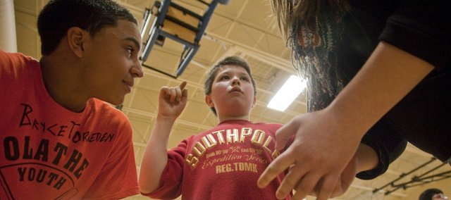 Logan Adair, 11, center, gives instructions to his eighth-grade teammates, Bryce Torneden, left, and Lauren Johnson, right,  during a basketball clinic Wednesday, Feb, 29, 2012, at West Middle School. Basketball players with the eighth grade West Middle School Warhawks team worked with younger special education students in the clinic after school.