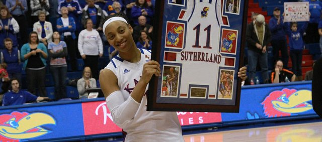 Kansas forward Aishah Sutherland holds a frame of memories after being honored on Senior Night on Wednesday night at Allen Fieldhouse.