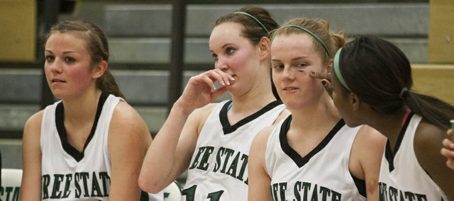 Free State sophomore Scout Wiebe (22) holds still while junior A'Liyah Rogers, right, checks out a cut under her eye that she received during Free State's first round sub-state game against Olathe North on Wednesday, Feb. 29, 2012, at FSHS. The Firebirds won, 57-42, and will face Olathe South on Saturday in Leavenworth.