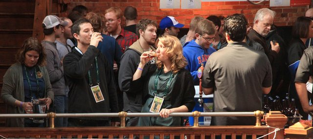 John Bourneuf, left, of Lawrence, and Maria Vopat, of Mission, have a taste of the Kansas Craft Brewers Exposition on Saturday, March 3, 2012, at Abe and Jake's Landing, 8 E. Sixth St., among hundreds of other beer enthusiasts.