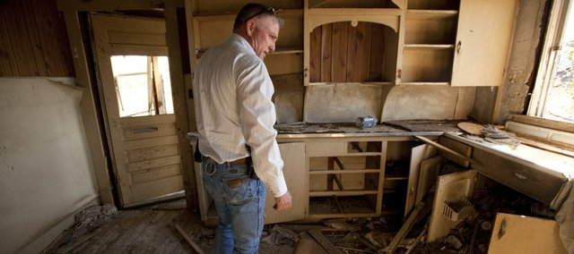 "Montgomery County Sheriff Bobby Dierks walks through a ramshackle farmhouse Feb. 24 that he says is a hot spot for methamphetamine cooks. Kansas has seen a surge in meth-lab incidents, from 143 in 2010 to 187 in 2011. Officials attribute the increase to the ""one-pot"" or ""shake and bake"" method of preparing the drug."