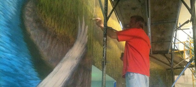 Lawrence artists Randall Bennett works on a mural of the Flint Hills he created for the Flint Hills Discovery Center in Manhattan. Bennett has been working on the mural since May. The center is slated to open April 14.