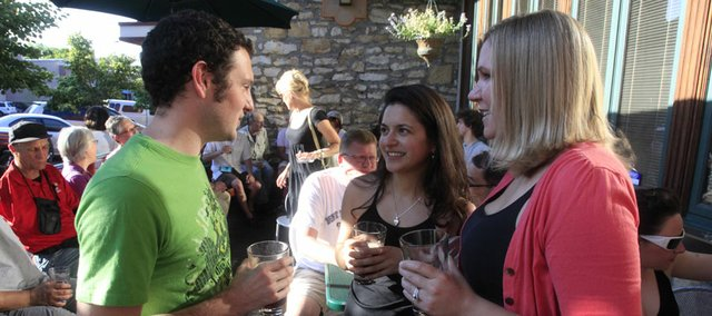 Hanging out on the Free State Brewing Co. porch are, from left, Patrick Stallbaumer, Joy Friedman and Julie Shrack in this 2009 file photo. Happy hour was reinstated in Kansas on July 1, 2012.
