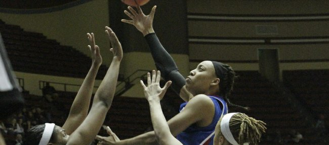 Kansas' Aishah Sutherland skies over a pair of A&M defenders during their Big 12 tournament game on Thursday, March 8, 2012, at Municipal Auditorium in Kansas City, Mo.