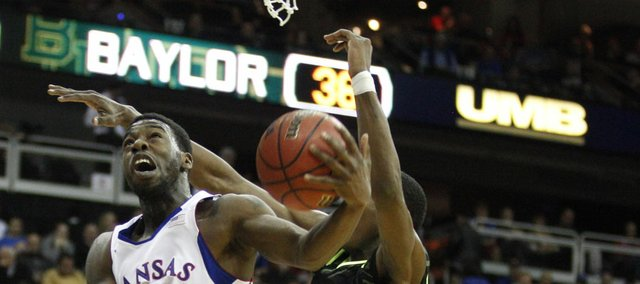 Kansas guard Elijah Johnson has a shot knocked away by Baylor forward Quincy Miller during the first half on Friday, March 9, 2012. At right is Baylor forward Quincy Acy.