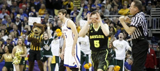 Kansas center Jeff Withey looks to the bench as Baylor guard Brady Heslip celebrates a big three-pointer to widen the Bears' lead during the second half on Friday, March 9, 2012.