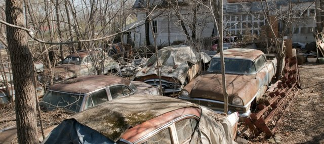 Fifteen deteriorating Packard automobiles are in a partially fenced backyard at 1106 Rhode Island, just east of the Judicial and Law Enforcement Center. City commissioners Tuesday started the process of declaring the property at 1106 Rhode Island unsafe and in need of demolition.
