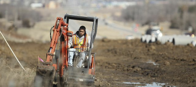 Eli Gomez, a worker with JT Underground, uses a mini excavator to dig a trench for fiber optic cable south of Lawrence, in preparation for the widening of Highway 59 on Monday, March 12, 2012.