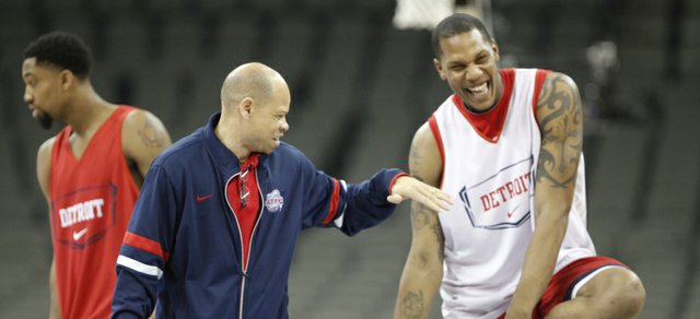 Detroit head coach Ray McCallum reaches out to slap hands with center Eli Holman as the Titans start their practice at Century Link Center in Omaha.