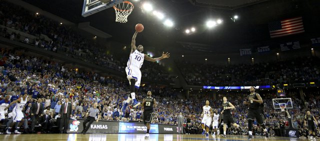 Kansas guard Tyshawn Taylor soars in for a breakaway jam to cap off the game for the Jayhawks with seconds remaining against Purdue on Sunday, March 18, 2012 at CenturyLink Center in Omaha.