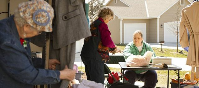 Jody Steiner, right, helps Eudora resident Peggy Brizendine check out while Velma Jahn, Eudora, browses through clothes during a garage sale at 3018 Harper St. on Saturday, March 10, 2012.