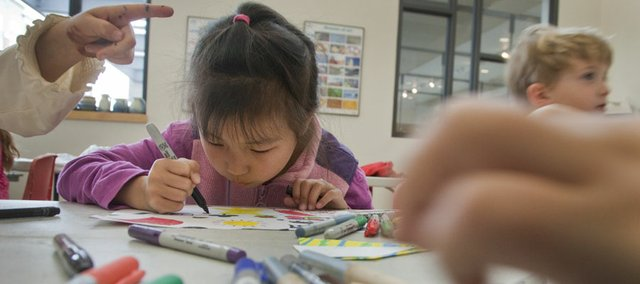 Yifan Wang creates colored stickers during a spring break guerrilla art workshop Tuesday at the Lawrence Arts Center. Children in the workshop created temporary artwork that they could leave in public places for others to enjoy.