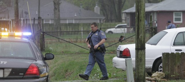 Armed Douglas County Sheriffs deputies exit the yard of a house in the 1700 block of east 1500 Rd. south of the Kansas Turnpike, where Russell Dean Baston was taken into custody Wednesday, March 21, just before 1 p.m.