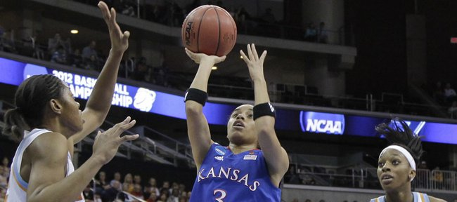 Kansas guard Angel Goodrich (3) shoots over Tennessee forward Vicki Baugh, left, and Glory Johnson in the first half of Saturday's game in Des Moines, Iowa.