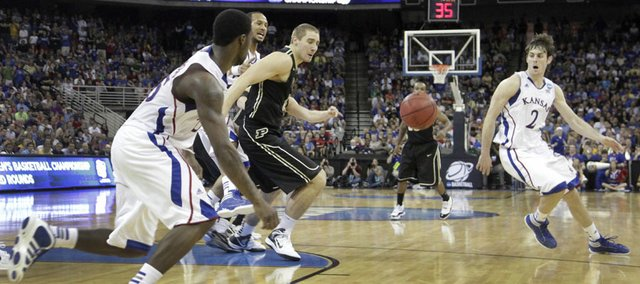 A loose ball rebound is suspended, between KU's Elijah Johnson, left, Conner Teahan, right and Purdue's Sandi Marcius, center, with 1:06 left on the game clock. This photo and next frame of Johnson securing the rebound, also taken at 1:06, demonstrates how, high-speed photography viewed in sequence can reveal what the human eye can not detect.