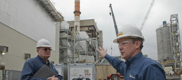 Lawrence Energy Center plant manager Troy Mussetter, left, and Paul Wallen, executive director, major construction projects, at Westar Energy, tour the construction site of a new $325 million environmental retrofit. The current project will reduce emission of fine particles from two of the three coal-burning units. Pictured in the background is unit five, where Westar is installing a fabric filtration system and rebuilding the sulfur dioxide scrubber system.