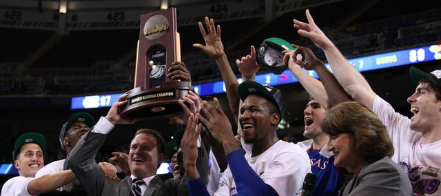 Kansas players crowd around head coach as they are presented with the Midwest Regional trophy as they celebrate the Jayhawks' 80-67 win over North Carolina to advance to the Final Four on Sunday,  March 25, 2012 at the Edward Jones Dome in St. Louis.