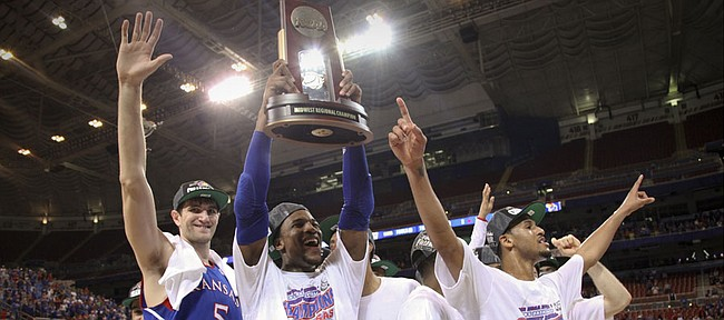 Kansas forward Thomas Robinson hoists the Midwest Regional trophy as he and teammates Jeff Withey and Travis Releford celebrate the Jayhawks' 80-67 win over North Carolina to advance to the Final Four on Sunday,  March 25, 2012 at the Edward Jones Dome in St. Louis.