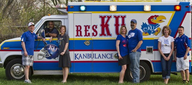 Owners of the Kanbulance, from left, Paul Wallen, Kitcha Paranjothi, Adrienne Paranjothi, Lisa Leroux-Smith, Wes Smith, Amy Clark and David Clark, all of Lawrence, stand next to their pride and joy: an ambulance that has been converted into the ultimate Jayhawk tailgating machine.