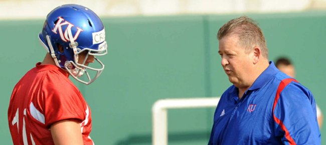 Kansas University quarterback Dayne Crist, left, listens to KU coach Charlie Weis during spring drills on Tuesday, March 27, 2012, at the practice fields south of Memorial Stadium.