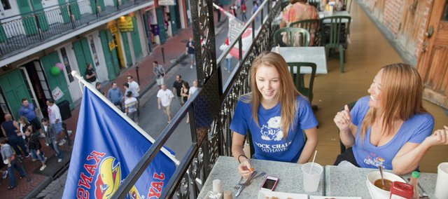 Ashley Falkner, left, an incoming Kansas University freshman from Olathe, and her mother, Julie Falkner, a 1990 KU graduate, eat  on the balcony, and near a Jayhawk flag, Thursday at Embers restaurant, overlooking Bourbon Street in the French Quarter of New Orleans. The two were with a friend and Julie's husband, Michael, also a 1990 graduate. The Falkner family attended the 2008 championship game in San Antonio, and the parents were students when KU won the championship in 1988.