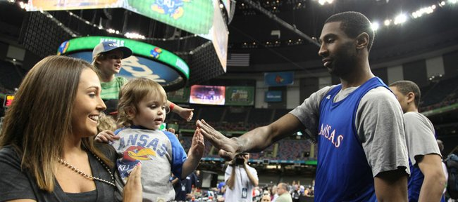 Kansas forward Justin Wesley gives a five to young Jayhawk fan Quinn Haggard, 2, as she and her mother, Carlyn Haggard greet the Jayhawks as they take the court for practice at the Superdome on Friday, March 30, 2012.