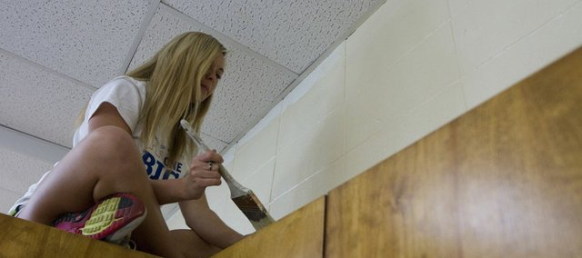 Shawnee freshman MacKenzie Rex finds a spot on top of a cabinet as she paints a classroom at Woodlawn Elementary School Saturday, March 31, 2012. Rex was taking part in The Big Event, in which KU students volunteer all across Lawrence doing things such as painting, gardening and weeding.