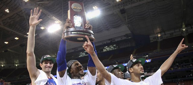 Kansas forward Thomas Robinson hoists the Midwest Regional trophy as he and teammates Jeff Withey (5) Travis Releford, right and Tyshawn Taylor celebrate the Jayhawks' 80-67 win over North Carolina to advance to the Final Four on Sunday,  March 25, 2012 at the Edward Jones Dome in St. Louis.