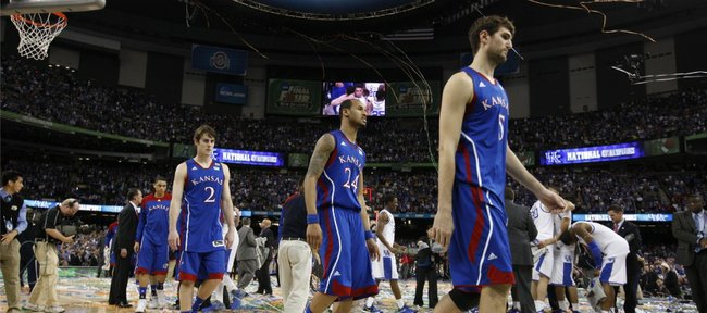 Kansas players Jeff Withey, front, Travis Releford and Conner Teahan leave the court as the Kentucky players celebrate their 67-59 national championship win on Monday, April 2, 2012 in New Orleans.
