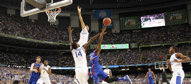 Kansas guard Tyshawn Taylor can't get off a shot under the defense of Kentucky forward Anthony Davis and Michael Kidd-Gilchrist during the first half of the national championship on Monday, April 2, 2012 in New Orleans.