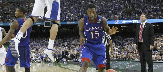 Anthony Davis (23) left, forces Elijah Johnson into a traveling foul late in the second-half of KU's 67-59 loss to Kentucky in the championship game Monday, April 2, 2012.