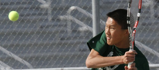 Free State junior Richard Lu hits a return against a Lawrence High opponent during the city showdown tennis dual on Tuesday, April 10, 2012, at FSHS.