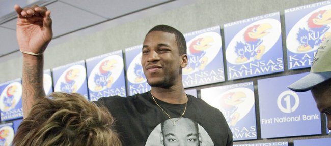 Kansas junior basketball player Thomas Robinson waves to the crowd after he declared for the NBA Draft on Monday during a press conference with KU coach Bill Self and Robinson's sister Jayla, pictured at right.