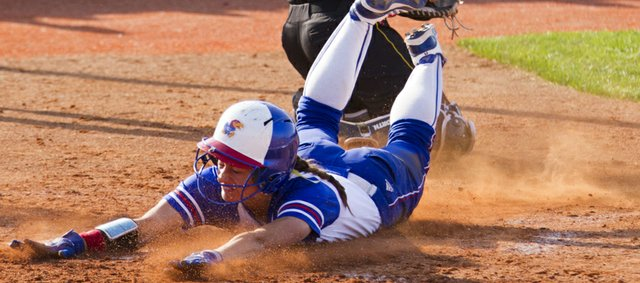 Kansas' Maggie Hull slides head-first past Wichita State catcher Brianne Bond for a score during the first game of a doubleheader against Wichita State on Wednesday, April 11, 2012, at Arrocha Ballpark.