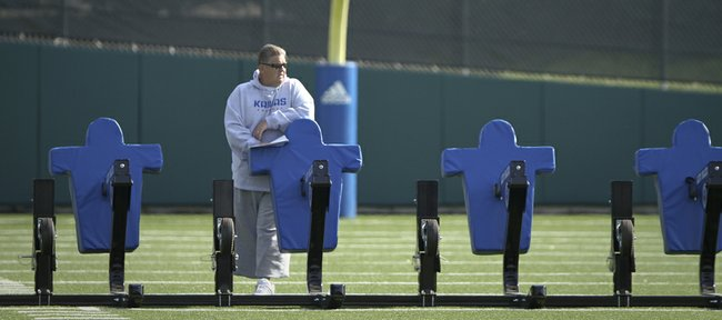 Kansas head coach Charlie Weis watches over practice from across the field on Tuesday, April 10, 2012.