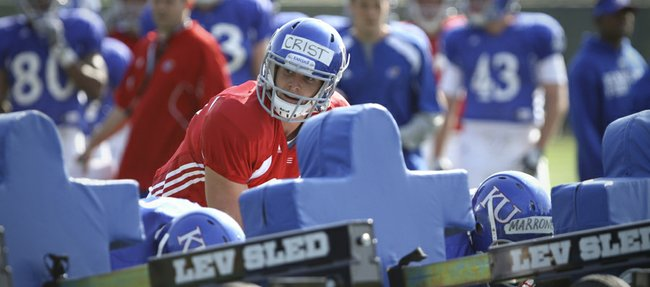 Kansas quarterback Dayne Crist gets down with the offensive line behind the sled as the unit runs through drills during practice on Tuesday, April 10, 2012.