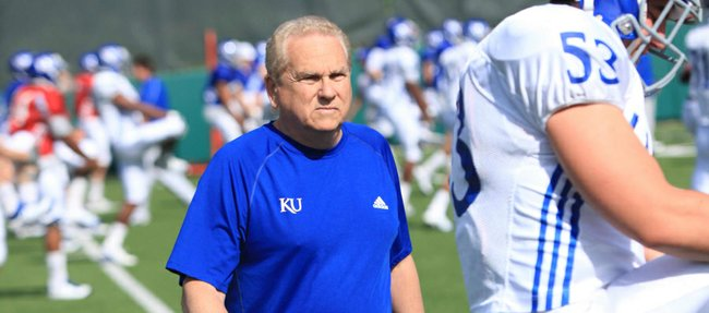 Defensive coordinator Dave Campo takes a close look at linebacker Ryan Karlin during Kansas University football practice on Tuesday, April 17, 2012.