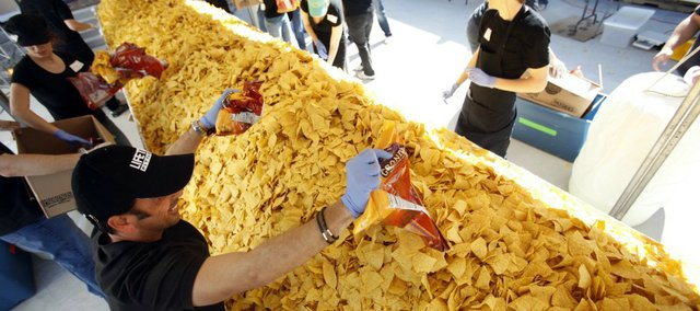 In this April 7, 2010, photo, workers put the finishing touches on what would soon be the world's largest nacho plate, in Frisco, Texas. On Saturday, Kansas Athletics looks to claim the record by serving a 4,600-pound plate of nachos.