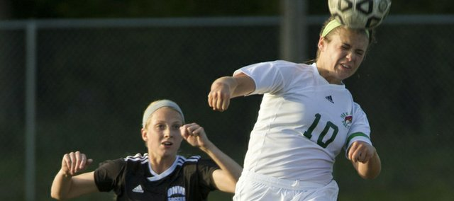 Free State's Kylee Loneker (10) uses her head to keep the ball away from Olathe Northwest's Hannah Kaloupek (16) during their  match Tuesday, April 17, 2012 at FSHS.