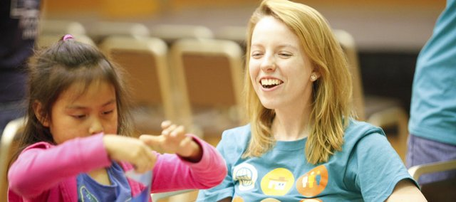 Kansas University sophomore Jen Rosacker, of Topeka, a coordinator for MILK (Mentors in the Lives of Kids), laughs as Emma, 5, has a little trouble with tape stuck to her fingers during the Music Madness event April 6 in the Kansas Union Ballroom.