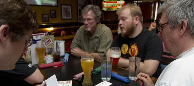 Members of the Team Channel Four news Team, from left, Matt Parker, George Parker, Patrick Funston and Arnie Knudson, all of Lawrence, work out an answer to a question as they play trivia April 15 at Bigg's Barbecue, 2429 Iowa.