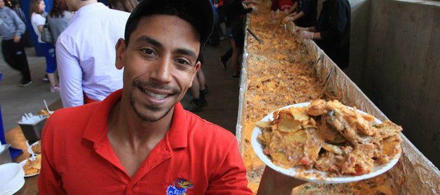 Eddie Diaz, of Centerplate, holds one of the hundreds of plates of nachos that came from an 80-foot-long tray Saturday at Memorial Stadium. The 4,689-pound nacho plate landed Lawrence a spot in the Guinness Book of World Records.