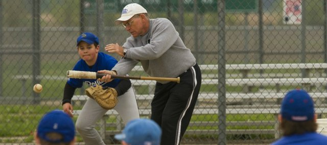 Former Lawrence High School baseball coach Ron Garvin simulates a bunt during a little league baseball practice Saturday, April 7, 2012 at the YSI sports complex. Garvin helps coach his grandson's baseball team.