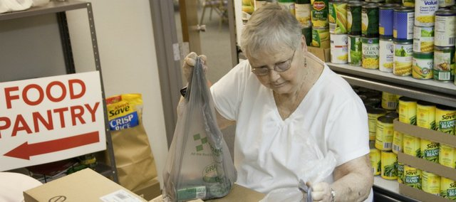Katie Studebaker is president of Lawrence Interdenominational Nutrition Kitchen, and she also started the food pantry operation at First Christian Church. Studebaker helps stock the pantry with other volunteers recently at the church.