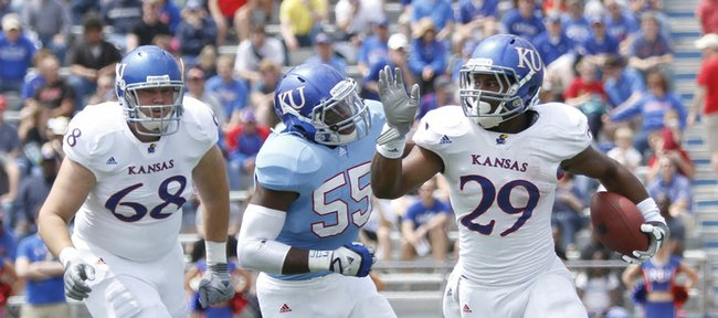 Kansas linebacker Michael Reynolds (55) chases after running back James Sims (29) during the second half of the Spring Game on Saturday, April 28, 2012 at Kivisto Field. At left is white team offensive lineman Luke Luhrsen.