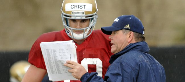 In this file photo from April 7, 2010, Notre Dame coach Brian Kelly talks to former Irish quarterback Dayne Crist, left, during practice in South Bend, Ind.