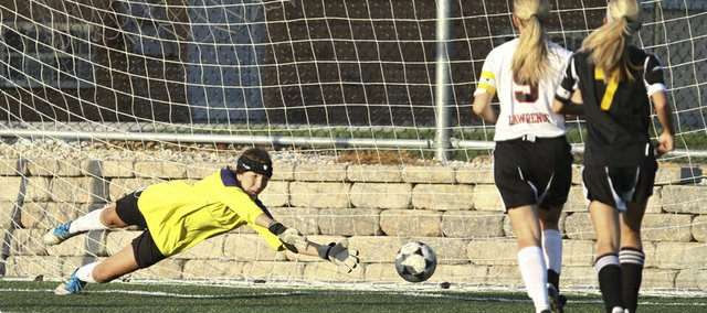 Lawrence High goalie Alex Ewy dives but can't stop a shot from Shawnee Mission West during the first half on Tuesday, May 8, 2012 at Lawrence High School.