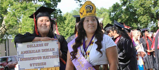 Randi Begaye and Monique Burnside, who is Miss Haskell, get ready to lead the commencement procession Friday for Haskell Indian Nations University.
